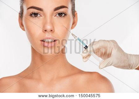 Close up of a beautiful young woman gets beauty injection in eye area with syringe isolated on white background