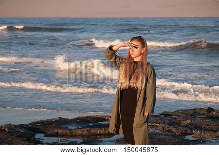 Beautiful view of ocean woman looking at the sea during the sunset on the beach in autumn