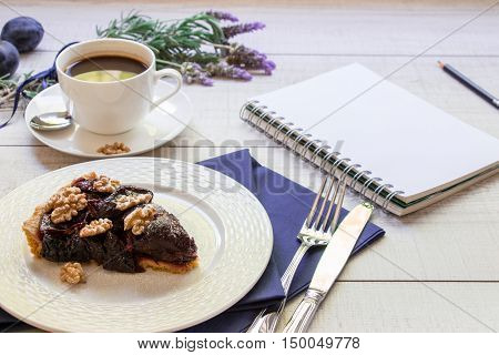 Left plum cake on a white plate next to a cup of coffee plums lavender bouquet knife and fork empty page of notebook on light wood background. A piece of plum cake and notebook. Horizontal.