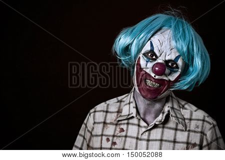 portrait of a scary evil clown wearing a ragged and dirty shirt with blood stains and a blue wig, against a dark background