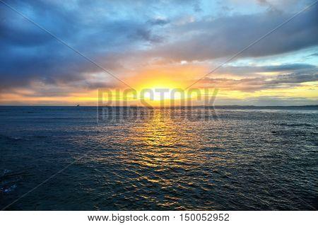 Por do Sol em meio  a nuvens sobre o oceano