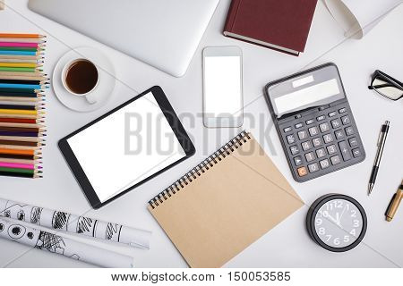 Top view of modern office desktop with white tablet cellular phone closeup laptop computer calculator coffee cup supplies and other items. Mock up