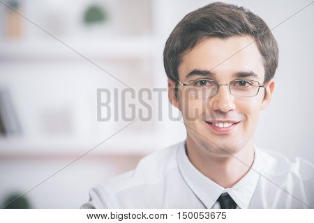 Closeup portrait of handsome young businessman in glasses white shirt and tie on blurry background