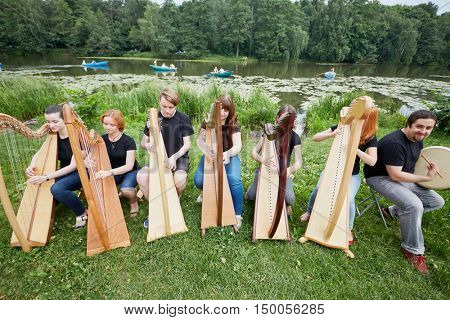 Ensemble of seven musicians play celtic harps performing outdoors at pond shore.