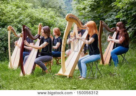 Ensemble of six young musicians performs outdoors in park at grassy lawn.