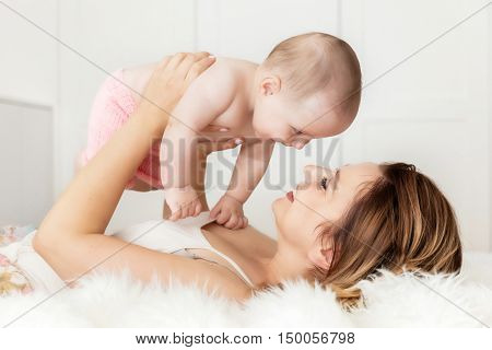 Mother with her newborn baby daughter. Candid emotions of maternity love. Soft backlight