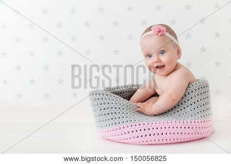 Cute baby sitting happy and laughing in a woollen basket. Wearing a flower headband. Child room wallpaper in grey stars.
