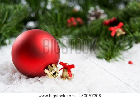 Close up of red christmas ball with fir branches in background. Still life of christmas decoration with small christmas bell on snow. Xmas holiday and winter concept.