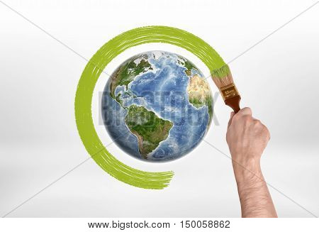 Man's hand encircles globe with a brush with green paint. Protection of the planet. Save planet. Environment and ecology.