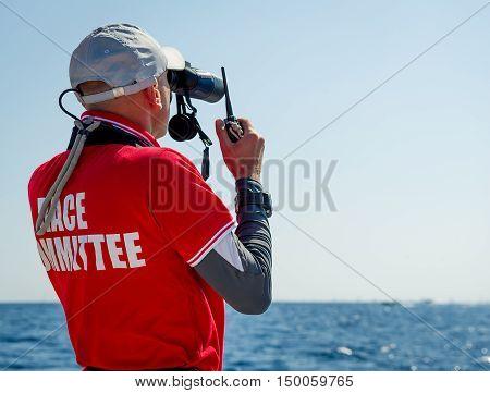 Sailing race referee is watching at his binocular, and talking by marine VHF radio. Sardinia, Italy.
