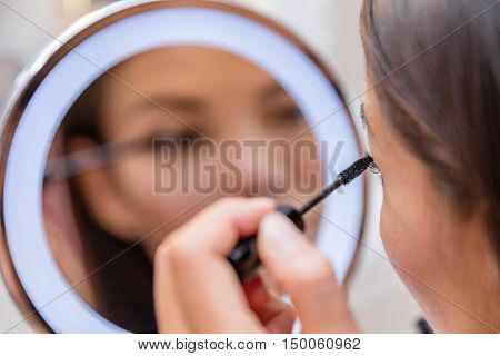 Woman putting mascara in lighted round makeup mirror from luxury hotel or home bathroom. Beautiful Asian girl getting ready for a night out applying eye make-up with brush looking at reflection.