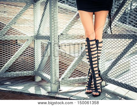 Fashionably dressed woman posing in boots, high-heeled gladiators in short black dress. Fashion and Style. On the background fence grid. Front view.