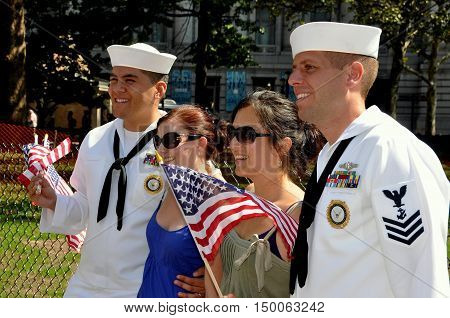 New York City - September 4 2009: Two women posing with two U. S. Navy sailors waving American flags in Battery Park