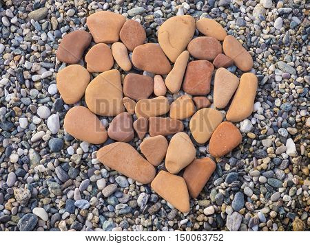 Stone heart shape with pebbles on beach