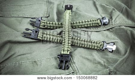 Military paracord bracelets on army-green fabric background