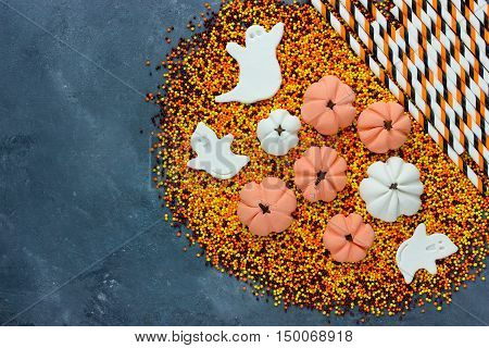 Halloween background traditional treats for kids on a stone background top view with copy space