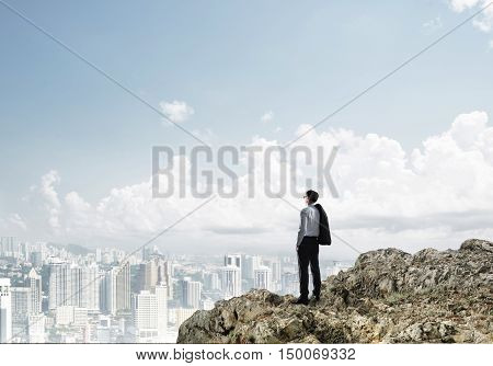 Elegant businesswoman standing on rock top and looking ahead