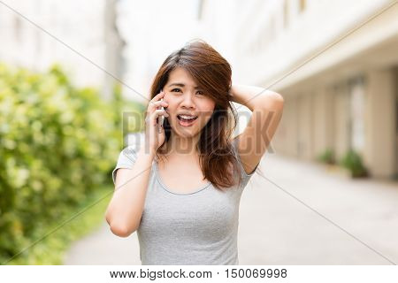 Young asian woman surprised and shocked while talking on smart phone.
