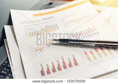 Financial documents and pen on laptop with sunlight filter effect.