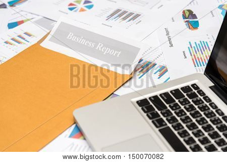 Business report and laptop on pile of financial graph and chart paper sheet.