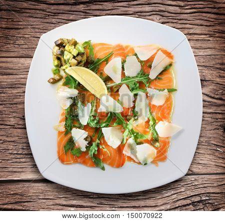 Salad with avacado, salmon, arugula and parmesan cheese.