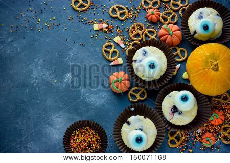 Halloween background healthy sweets and treats for kids funny one-eyed monster cakes creative food idea top view blank space for text