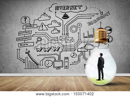 Businessman inside of light bulb in empty concrete room and sketches on wall