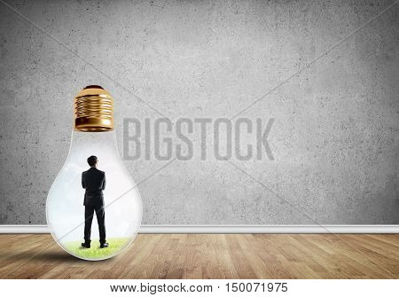 Businessman inside of light bulb in empty concrete room