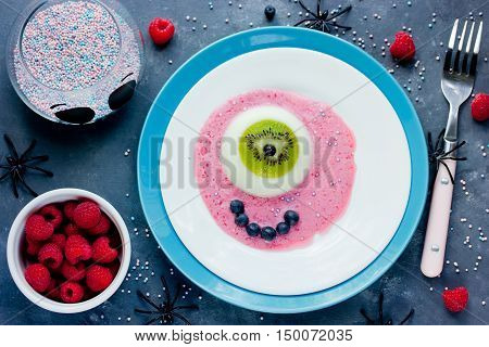 One eye panna cotta with kiwi fresh berries and sauce Halloween recipe. Creative idea for kids dessert on holiday party top view