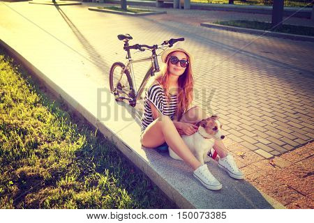 Smiling Hipster Girl with her Dog and Bike in Park. Happy Woman Enjoying Summer Lifestyle with Pet. Candid Toned and Filtered Photo with Copy Space.