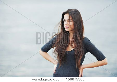 Beautiful long-haired woman peers into the distance on the shore of the Gulf of Finland the wind ruffled her hair.