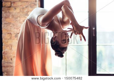 Graceful flexibility. Serious gifted brunette dancer bending backwards and moving her hands while concentrating on keeping her balance