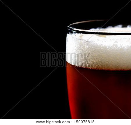 glass of dark beer with foam on a black background