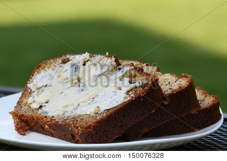 Banana bread on plate on outdoors at late afternoon individual servings sliced and buttered