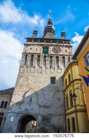 Tower bell of the famous medieval citadel in Sighisoara against the blue sky, in Sibiu - Romania
