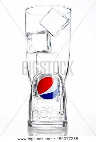 LONDON UNITED KINGDOM-OCTOBER 03 2016: Original empty pepsi cola glass with ice cubes. Pepsi is a carbonated soft drink that is produced and manufactured by PepsiCo. Created and developed in 1893.