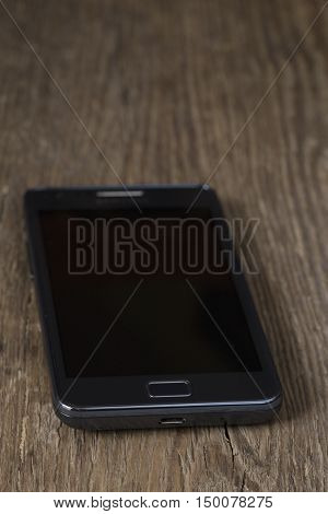 Black mobile phone on rustic  wooden background