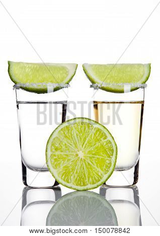 Silver and gold tequila shot glass with lime slice on white background