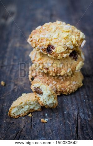Pile of homemade cornflakes and raisins cookies on old wooden table. Freshly baked corn flake cereal cookies on rustic background. Selective Focus.
