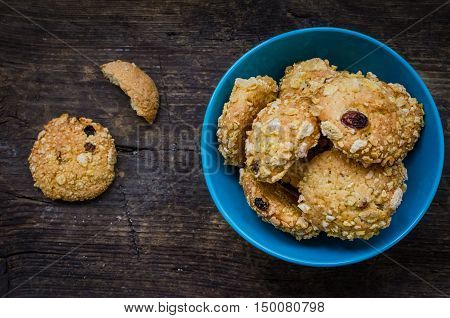 Pile of homemade cornflakes and raisins cookies in a blue bowl on old wooden table with place for text. Freshly baked corn flake cereal cookies on rustic background. Top view. Copy space.