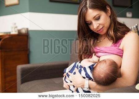 Portrait of a beautiful mother breastfeeding her newborn baby while sitting in a couch at home poster