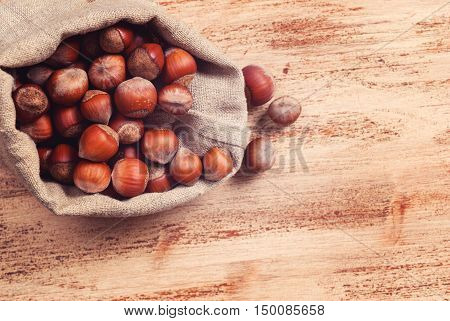The untreated nuts in shell in bag on wooden Board