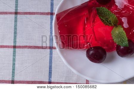 Strawberry jelly on the plate with ripe cherries