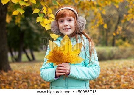 Little ginger girl holding a maple leaf in his hands in autumn park