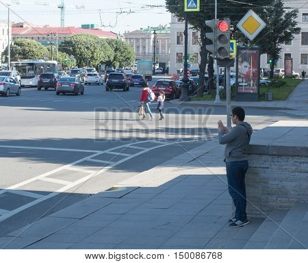 Saint Petersburg Russia September 12 2016: Young man photographing on the streets on a mobile phone in St. Petersburg Russia.