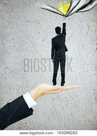 Male hand holding tiny businessman that is dragging abstract sketch on concrete background. Discovery concept