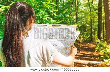 Woman In Reading A Map In The Forest