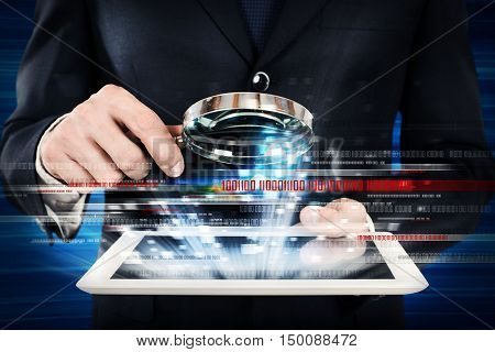 Man looks at the magnifying glass the screen of a tablet