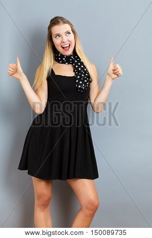 Happy Young Woman Giving Thumbs Up On Gray Background