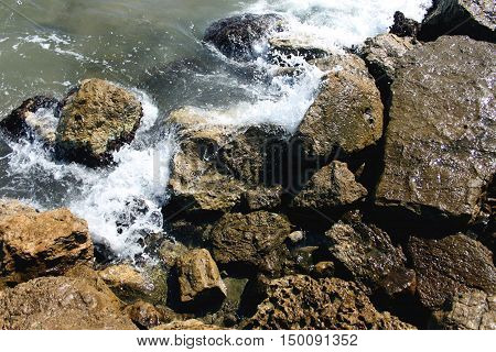 The waves of the sea beating against the sharp rocks and stones coast